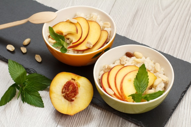 도자기 그릇에 복숭아, 캐슈 너트, 아몬드, 민트 잎을 넣은 수수 죽, 검은 돌판에 나무 숟가락. 신선한 과일을 곁들인 비건 글루텐 프리 수수 샐러드. 평면도.
