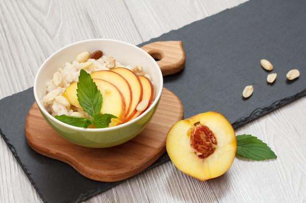 도자기 그릇에 복숭아, 캐슈넛, 아몬드 조각을 넣은 수수 죽, 나무와 돌판에 신선한 복숭아. 과일을 곁들인 비건 글루텐 프리 수수 샐러드.