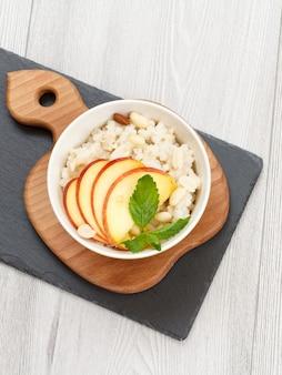 나무와 돌판에 있는 도자기 그릇에 복숭아, 캐슈넛, 아몬드 조각을 넣은 수수 죽. 과일을 곁들인 비건 글루텐 프리 수수 샐러드. 평면도.