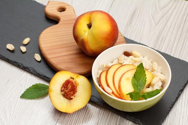 도자기 그릇에 복숭아, 캐슈넛, 아몬드 조각을 넣은 수수 죽, 나무와 돌판에 신선한 복숭아 전체. 과일을 곁들인 비건 글루텐 프리 수수 샐러드.
