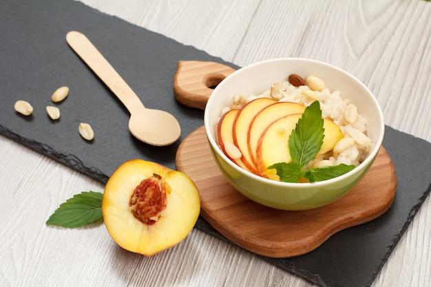 도자기 그릇에 복숭아, 캐슈넛, 아몬드 조각을 넣은 수수 죽, 나무와 돌판에 신선한 복숭아, 회색 배경. 과일을 곁들인 비건 글루텐 프리 수수 샐러드.