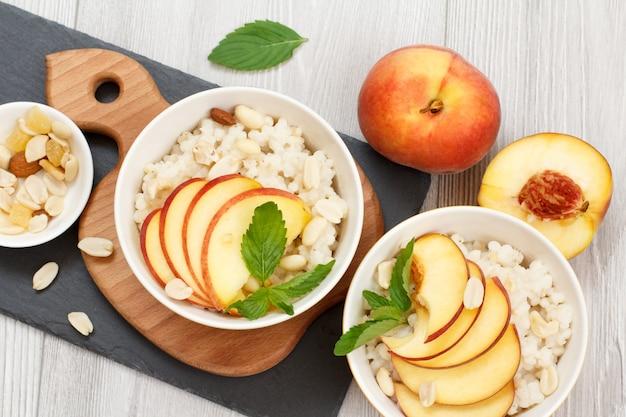 도자기 그릇에 복숭아, 캐슈넛, 아몬드 조각을 넣은 수수 죽, 나무와 돌판에 신선한 복숭아. 과일을 곁들인 비건 글루텐 프리 수수 샐러드. 평면도.