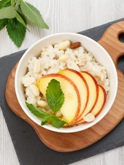 나무와 돌판에 도자기 그릇에 복숭아, 캐슈넛, 아몬드 조각을 넣은 수수 죽. 과일을 곁들인 비건 글루텐 프리 수수 샐러드. 평면도.