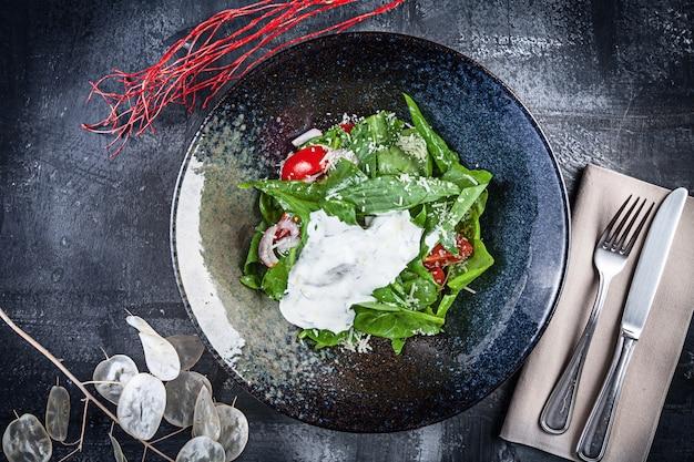 トマトとサワークリームのスイバサラダ。フラットレイアウトの食品。ランチにはフレッシュでグリーンなビーガンサラダ。上から暗い背景ビューに黒いボウルのサラダ。