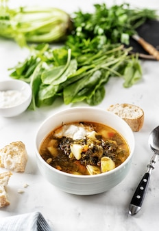 Sorrel soup with sour cream in white bowl