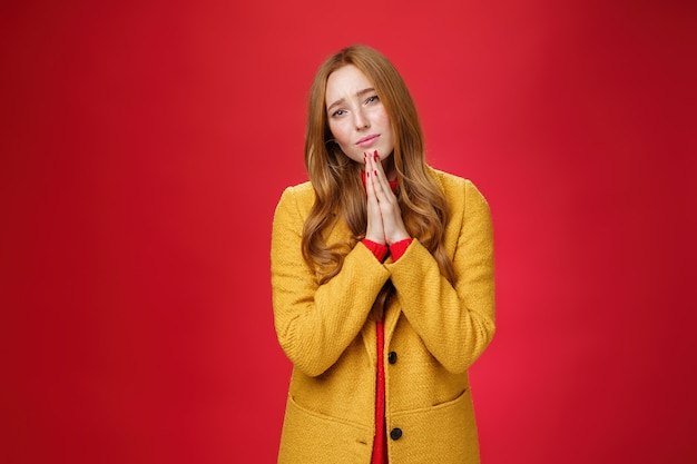 Sorrow and sad attractive redhead girlfriend in yellow coat begging for mercy standing hopeful and upset with hands in pray pouting and frowning, apologizing asking forgiveness over red background.