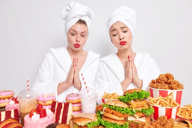 Sorrowful diverse women with pleading expressions keep palms pressed together look at appetizing junk food feel temptation to eat
