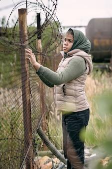 머리 스카프와 조끼를 입은 슬픈 중동 소녀