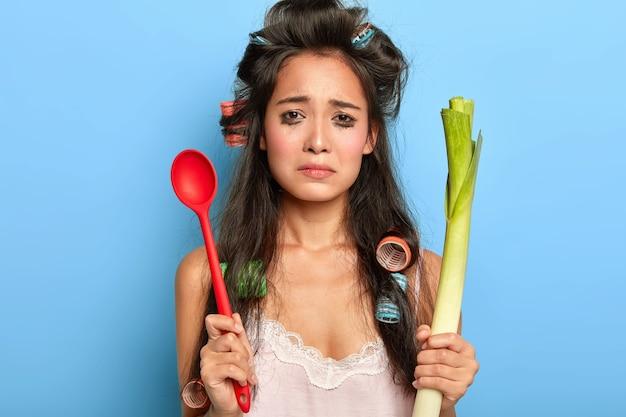 Скорбная несчастная женщина плачет от отчаяния, испортила макияж, держит красную ложку и зеленый лук-порей.