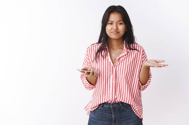 Sorry cannot help you. portrait of upset cute polynesian girl in striped blouse pursing lips and shrugging with raised hand in dismay holding smartphone feeling down lacking money bank account