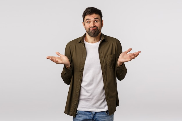 Sorry cant help. indecisive and clueless handsome bearded man in coat, shrugging with hands sideways, smirk puzzled, dont know anything, trouble answer, standing white background troubled