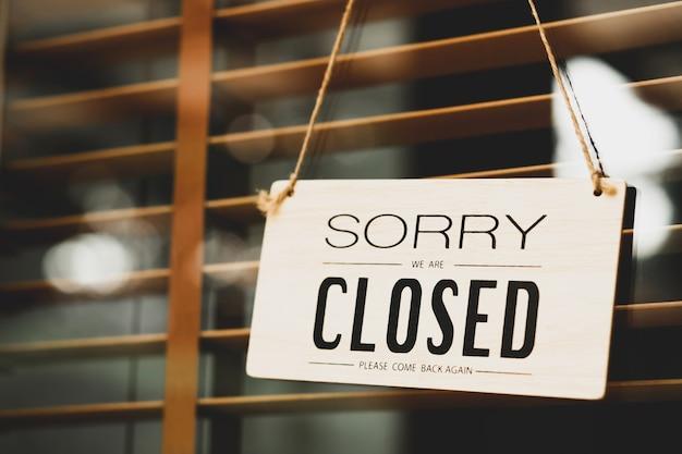 店のドアのサインを閉じて申し訳ありません。カフェフロントやレストランの文字が入り口のドアに掛かっています。ヴィンテージトーンスタイル。