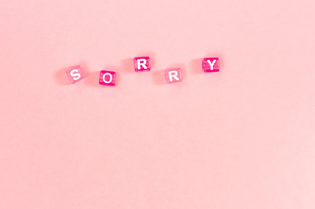 Sorry  inscription made of colorful cube beads with letters. festive pink background concept with copy space