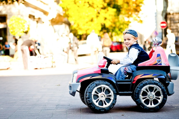 申し訳ありません、それは私ではありませんでした!小さなおもちゃの異国人の上の男の子が広場の周りをドライブ