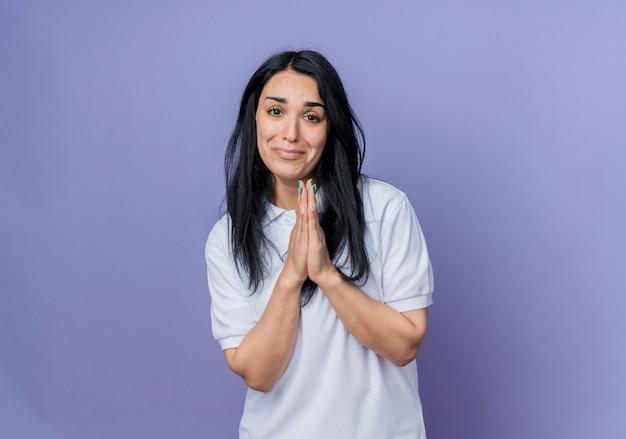 Извините, молодая брюнетка кавказская девушка держит руки вместе, изолированные на фиолетовой стене
