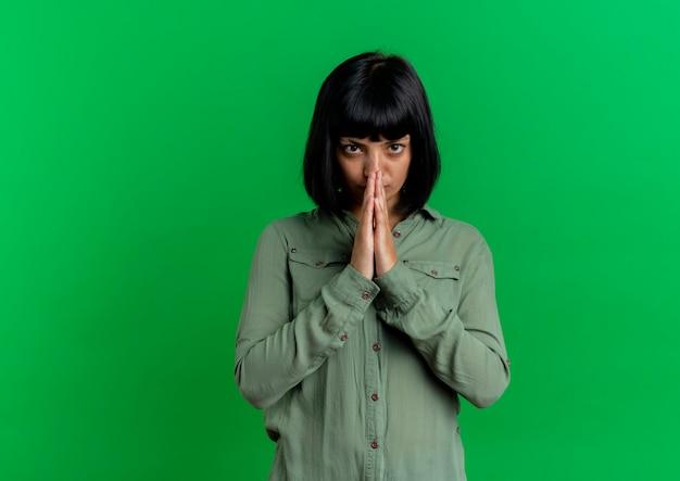 Извините, молодая брюнетка кавказская женщина держит руки вместе, глядя в камеру, изолированную на зеленом фоне с копией пространства