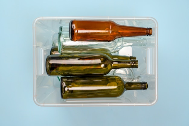 Sorting garbage. container with glass bottles of wine and beer on a blue background.