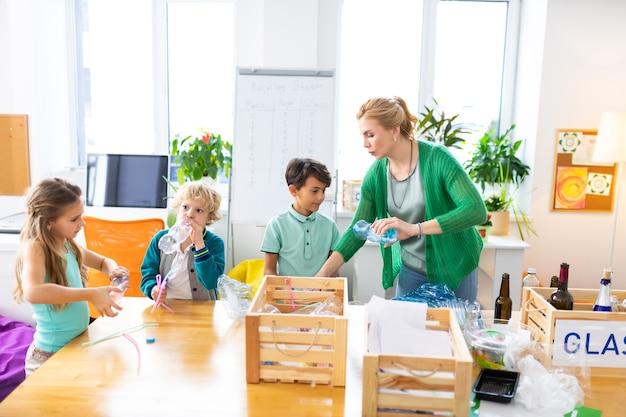 Сортировка помета. школьники и учитель сортируют мусор в просторном классе на уроке экологии