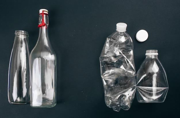 廃棄物の分別。 2つの空のガラスとペットボトルがリサイクル用に準備されています。リデュース、リユース、リサイクル。環境を守れ。上面図