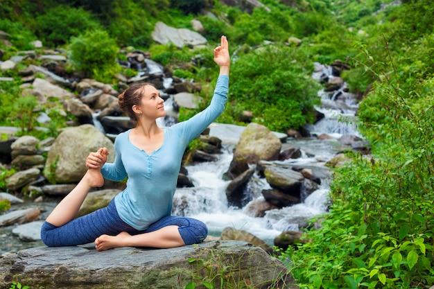 Sorty fit женщина делает асаны йоги на открытом воздухе на тропический водопад
