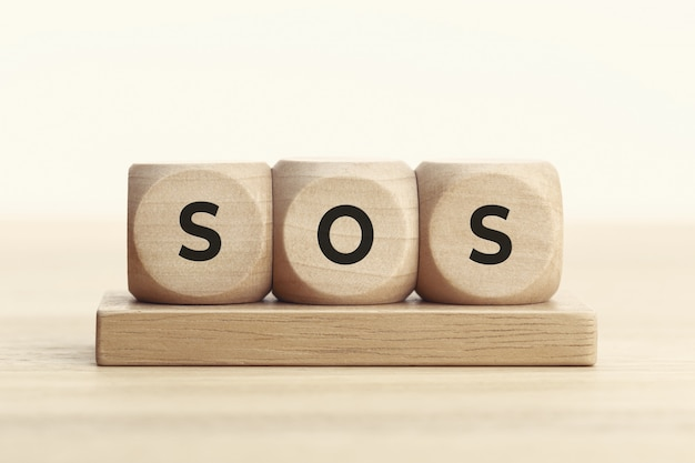 Sos concept. wooden block with text on table.