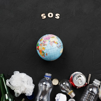 Sos letters, earth and pile of garbage on dark background