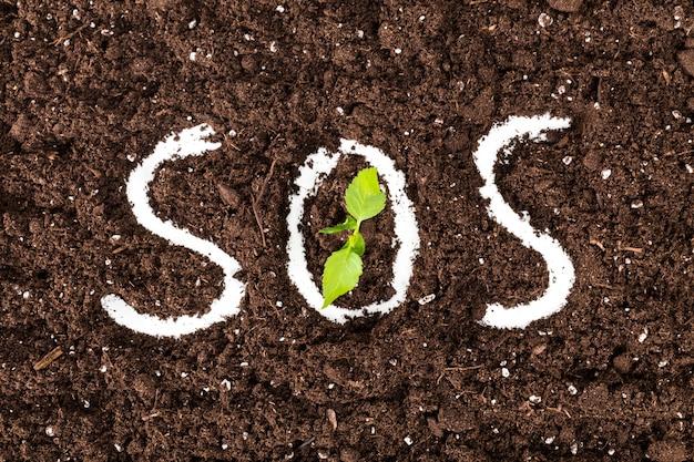 Sos text on black soil ground