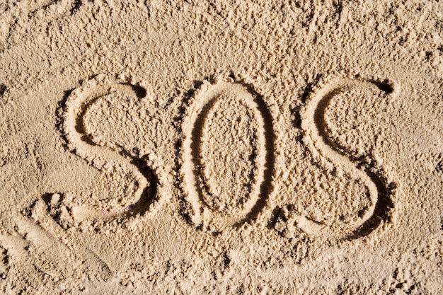 조개껍데기에서 모래에 새겨진 모래 해변에 그려진 sos 단어 sos 캠핑 하이킹 위험 표지판은...