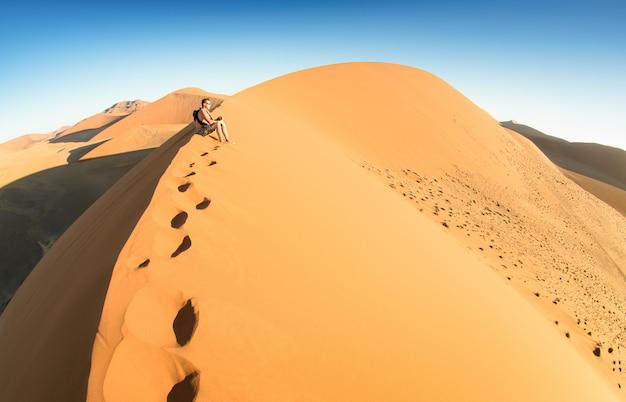 Sossusvleiナミビアの砂丘45で砂の上に座っている孤独な男性旅行者