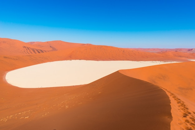 Sossusvlei namibia, clay and salt pan surrounded by majestic sand dunes. namib naukluft national park, main visitor attraction and travel destination in namibia.