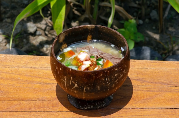 Soto batok a javanese beef soup served in a traditional bowl made of coconut shell