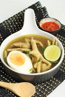 Soto cekerkuningまたはyellowchicken feet soupは、インドネシアの特別なスープです。伝統的なインドネシアのレシピで鶏の足のスープから作られました。ゆで卵添え