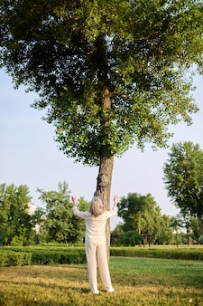 Soul practice. back view of blonde woman in trousers and blouse raising arms in front of tall green tree in park