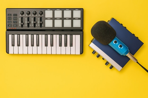 Sound card, music mixer and microphone on yellow background. the concept of workplace organization. equipment for recording, communication and listening to music.
