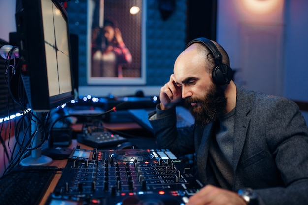 サウンドエンジニアは、スタジオで女性歌手の録音を行います。