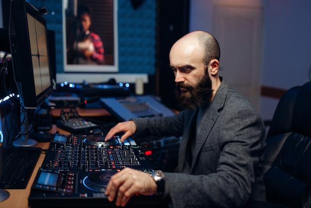 Звукорежиссер делает запись певца в студии