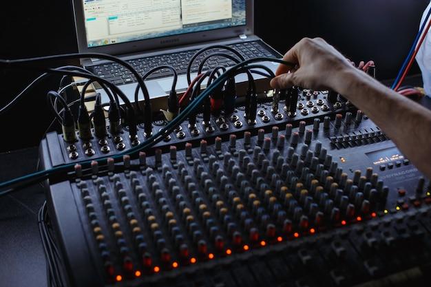 스튜디오 믹서에 잭 오디오 케이블을 연결하는 사운드 엔지니어.
