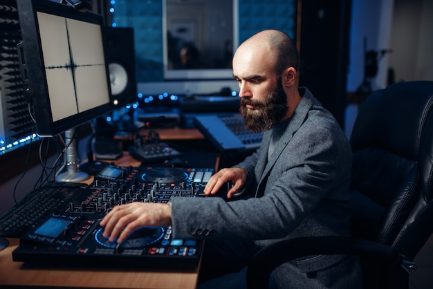 Sound engineer working at the remote control panel in the recording studio. musician at the mixer, professional audio mixing