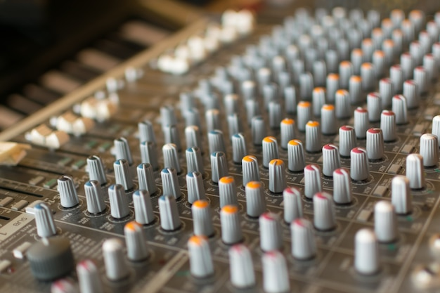 Sound mixer control board with volume buttons.