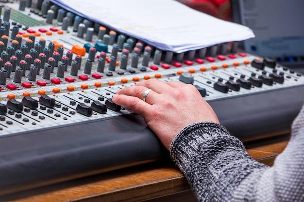 スタジオでのサウンドのミキシングおよび増幅装置。オペレーターが音響パワーを調整