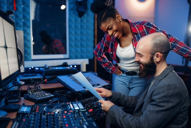 音声録音スタジオのリモートコントロールパネルでサウンドオペレーターと女性歌手。