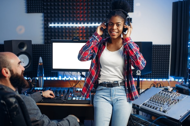 スタジオでのサウンドプロデューサーと女性パフォーマー