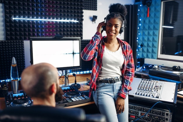Sound producer and female performer in headphones listens composition in recording studio.