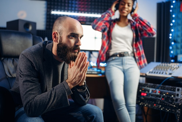 Sound producer and female singer in headphones listens composition in recording studio.