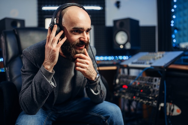 Sound producer in headphones listens composition of female singer in recording studio.