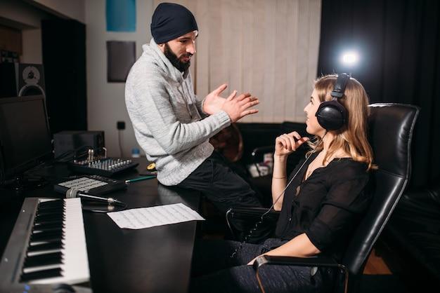 Звукорежиссер с певицей в музыкальной студии