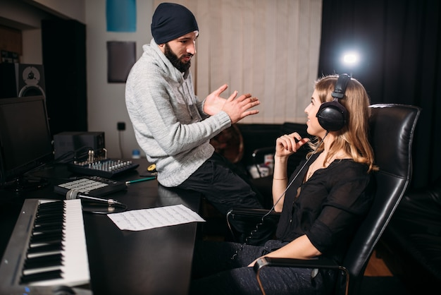 Sound producer with female singer in music studio
