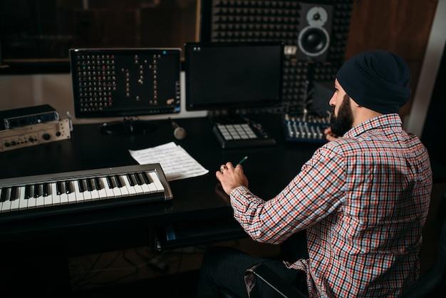 Звукорежиссер работает с аудиоаппаратурой в студии.