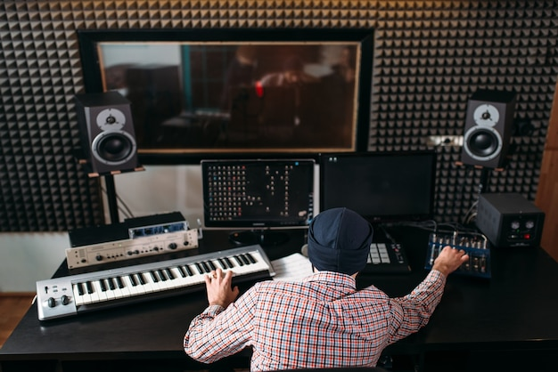 Sound producer work with audio equipment in studio.