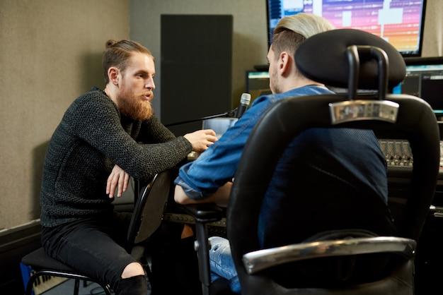 Работники студии звукозаписи разговаривают